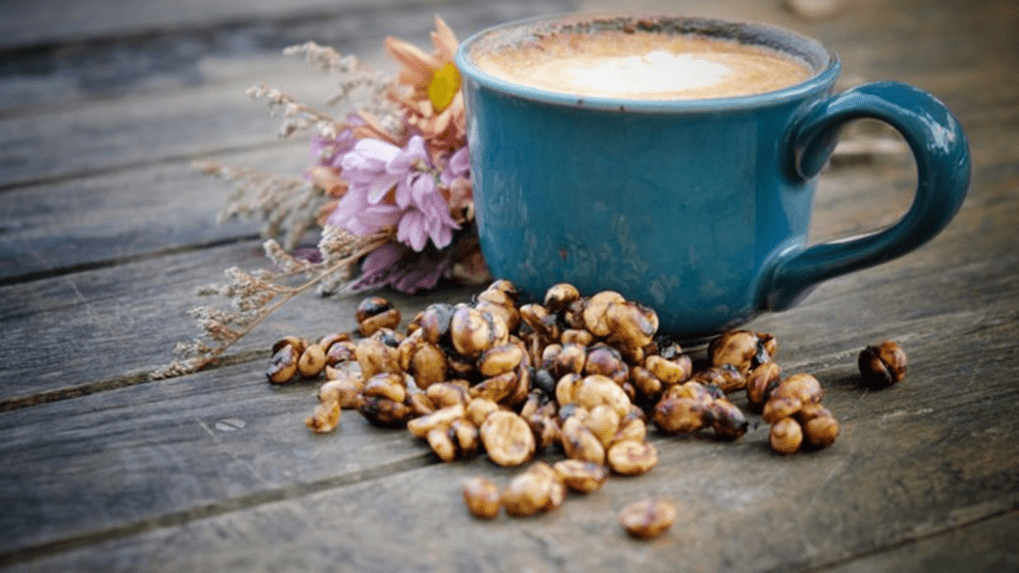 Cup of Coffee with Honey Processed Beans and flower laying beside