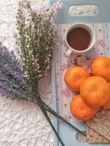 Coffee with pretty flowers and oranges to showcase its health benefits