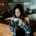 Girl drinking coffee in kitchen