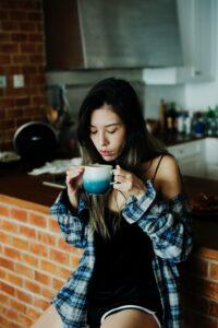 A girl drinking Coffee in a kitchen